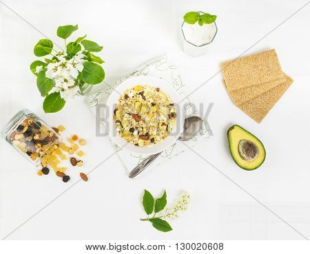 Healthy organic breakfast with muesli nuts raisin and smoothie yogurt. White background and spring flowers. Top view