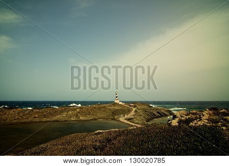 Lighthouse Cap de Favatrix on Stormy Sea Waves background Still Life. Northern Coast of Menorca Balearic Islands