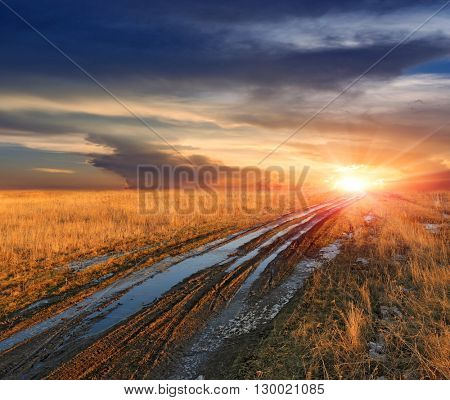 dirt road across meadow in steppe at sunset\