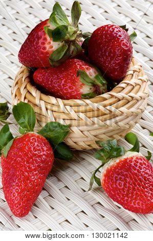 Heap of Fresh Ripe Strawberries in Wicker Bowl closeup on White Wicker background