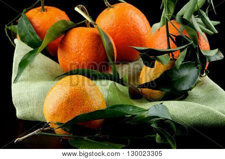 Arrangement of Ripe Tangerines with Leafs on Green Napkin closeup on Dark Wooden background
