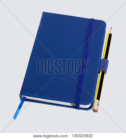 a blue notebook and pencil in light back