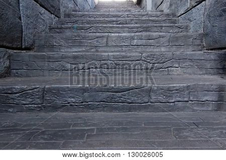 Ascending stairs made from stone. At the end there is a bright light. Conceptual.