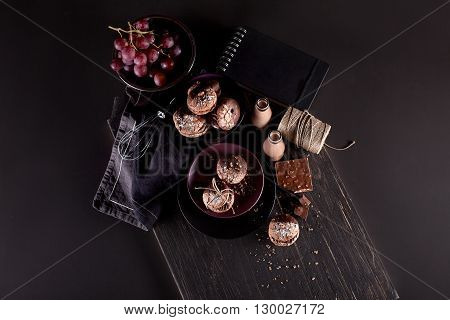 Italian maroni cookies on the plate and bowl with grapes chocolate milkshakes cloth notebook on dark old wooden background from the top