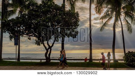 Honolulu, Hawaii, USA - Dec 15, 2015: Waikiki Beach and people doing recreational activities. Near the Kuhio Beach Hula Mound, along Kalakaua Avenue. Due to the promixity to the water, there is a slight haze caused by the tropical breeze. Image features s