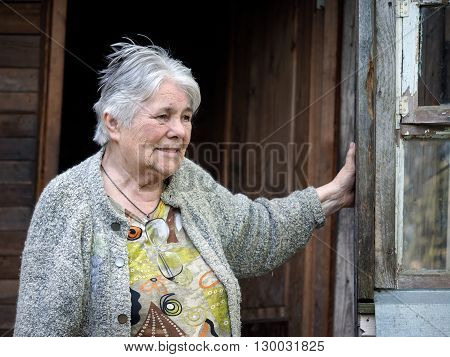 Portrait of an elderly woman. Old house doorway. Grandma smiles. The woman has gray hair, a lot of wrinkles.