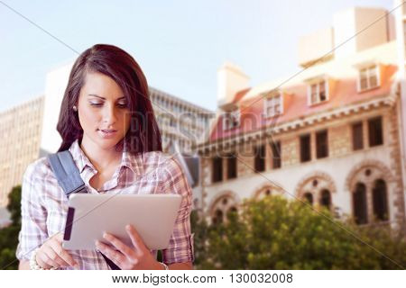 Low angle view of city buildings on sunny day against young focused student using a tablet computer
