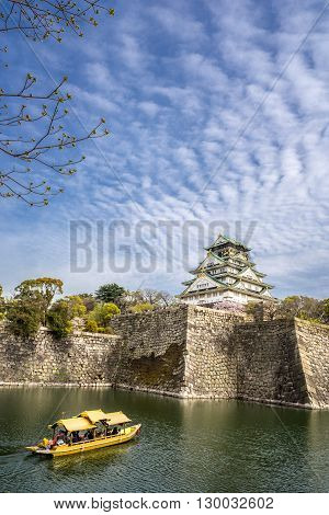 Osaka castle and a tourist boat in the city moat
