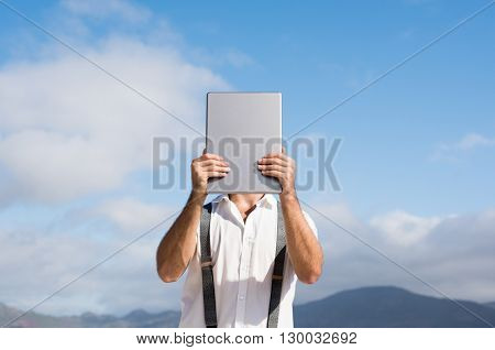 Young man covering face with digital tablet. Man hiding his face behind digital tablet while standing against clear sky. Portrait of a casual man holding digital tablet.
