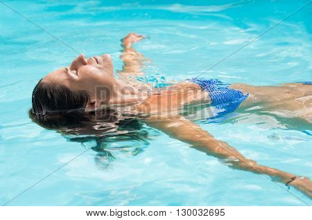 Young woman relaxing in swimming pool. Smiling woman with eyes closed lying on her back floating in a pool. Beautiful tanned woman in blue swimwear relaxing in swimming pool spa.