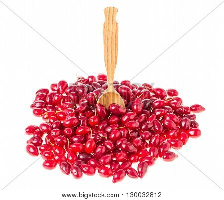 Ripe dogwood berries and wooden spoon. Isolated on a white background.