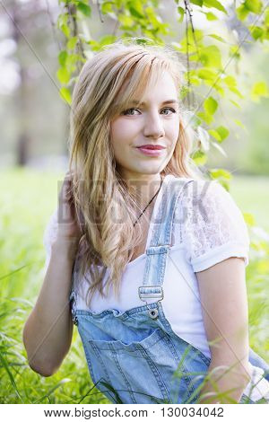 Young beautiful girl in overalls under the birch