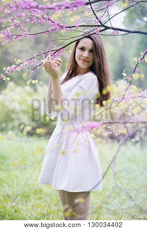 Beautiful woman in a spring garden under a blossoming tree
