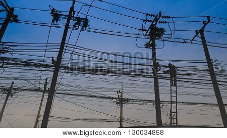 Electric post with chaotic foul cable power line wire and repairman on stairs on twilight blue sky/Electric post with chaotic power line and repairman