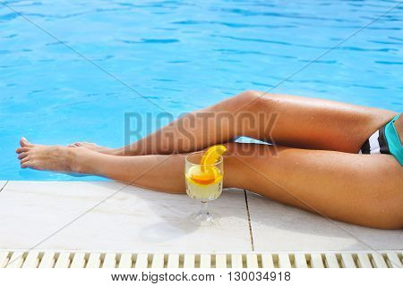 Pretty woman enjoying cocktail near the swimming pool. Close up