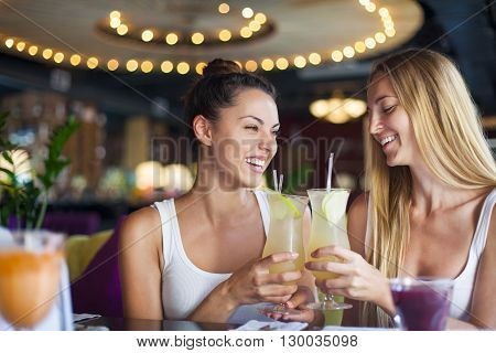 Two beautiful happy women having fun in a bar drinking cocktails