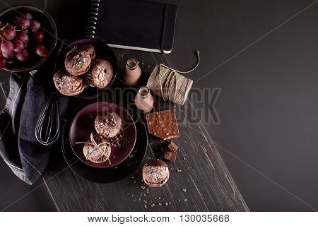 Italian maroni cookies on the plate and bowl with grapes chocolate milkshakes cloth notebook on dark old wooden background top view
