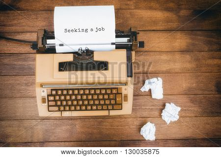 Seeking a job message on a white background against view of an old typewriter and paper