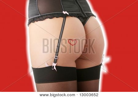 Sexy woman butt with drawn red heart isolated on red background