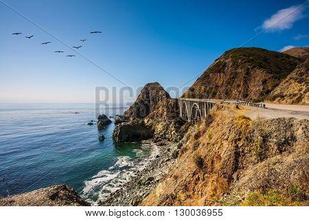 Scenic arch bridge - viaduct runs along the Pacific coast. In the sky flies a flock of cranes. California State Route 1, USA