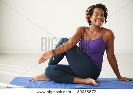 Cheerful African-American woman practicing asana in yoga class