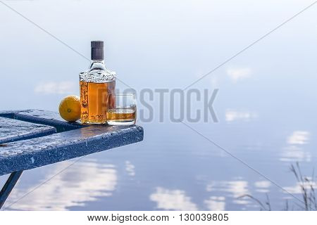 Bottle of tequila and tumbler with lemon on the shore of lake