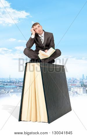 Man sitting on book and reading. Blue sky and city at background. Concept of reading