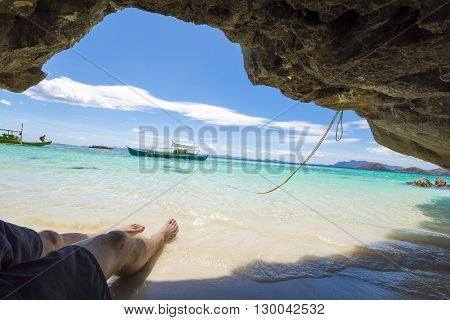 Relaxing under rocky outcrop on Banol Beach, Coron islands, Philippines