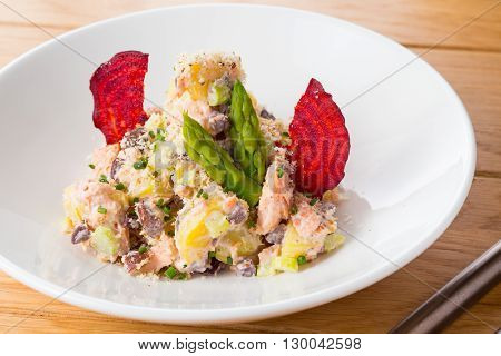 Salad of potatoes, beans, salmon decorated with chips of beets and asparagus on a white plate on a wood.