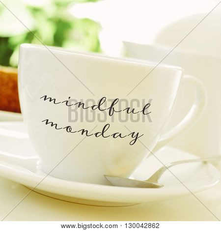 closeup of a cup of coffee or tea on a set table with the text mindful monday written in it