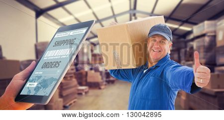 Man using tablet pc against forklift in a large warehouse
