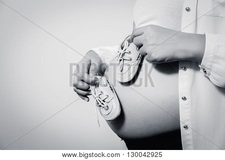 Small shoes for the unborn baby in the belly of pregnant women isolate white background.