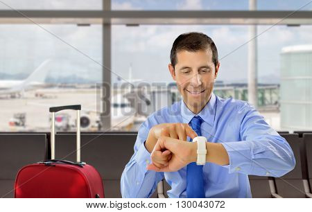 businessman looking his wrist watch at the lobby of airport