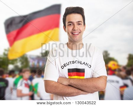 German fan with dark hair with other fans in the background