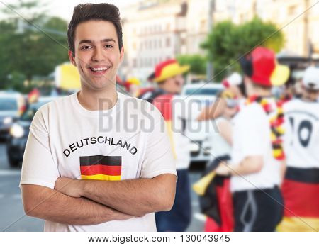 Laughing german fan with dark hair with other fans in the background