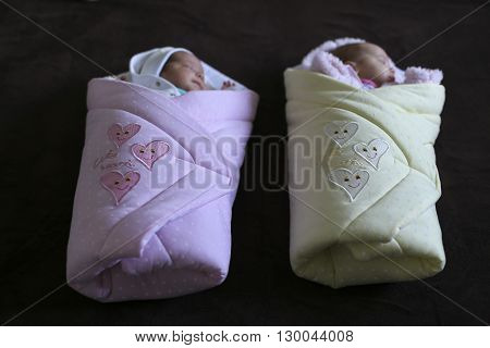 Baby twins in baby blankets ready for a walk on a dark background