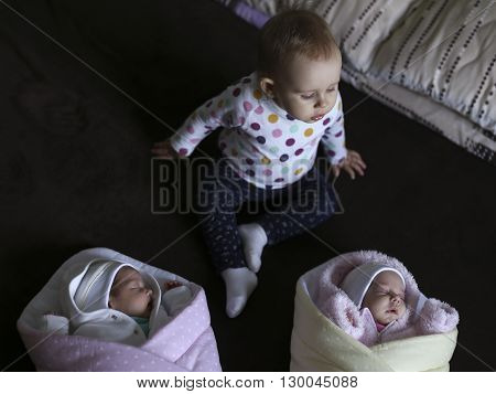 the newborn twins in a blanket with his year-old sister who oversees them