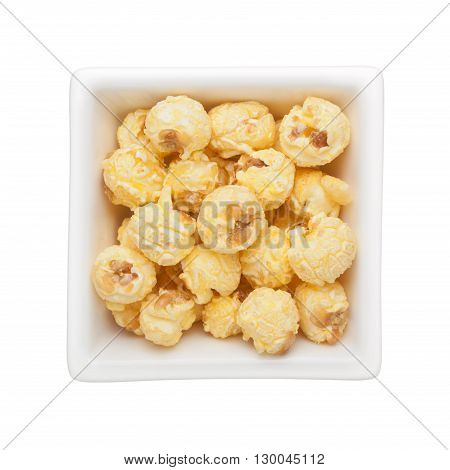 Caramel popcorn in a square bowl isolated on white background