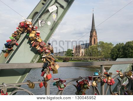 Lovelocks on the Eiserner Steg Bridge in Frankfurt, Germany with the Three Kings Church on the background