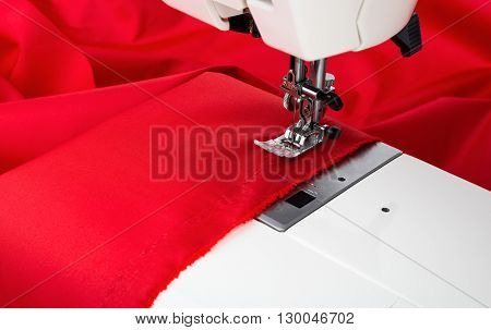 Sewing machine and red fabric isolated on white background