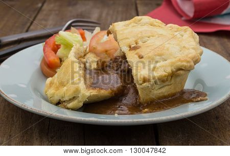 Steak pie and gravy close up on wood
