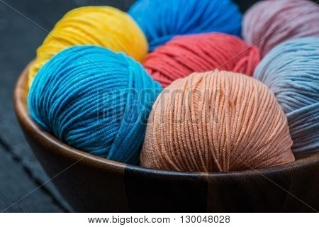 A lot of colorful knitting yarn balls in wooden basket