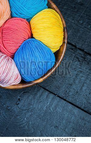 Balls of a colorful knitting yarn balls in basket