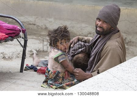 LEH INDIA - JUNE 29 2015: Unidentified poor Indian beggar family on street in Ladakh. Children of the early ages are often brought to the begging profession.