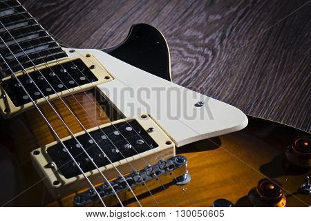 The vintage electric guitar on the wooden floor