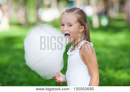 Cute girl with white cotton candy in the summer park