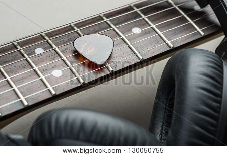Electric Guitar With Headphones And Mediator On A Brown Wooden Floor