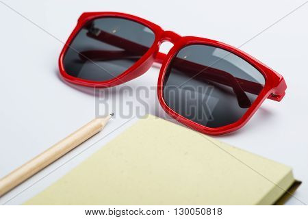 Red Sunglasses With Yellow Notepad And Pencil On White Surface