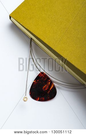 Yellow Notepad With String And Mediator On White Surface