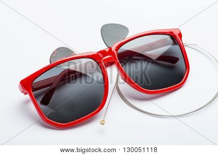 Red Sunglasses With Two Mediators And String On White Surface